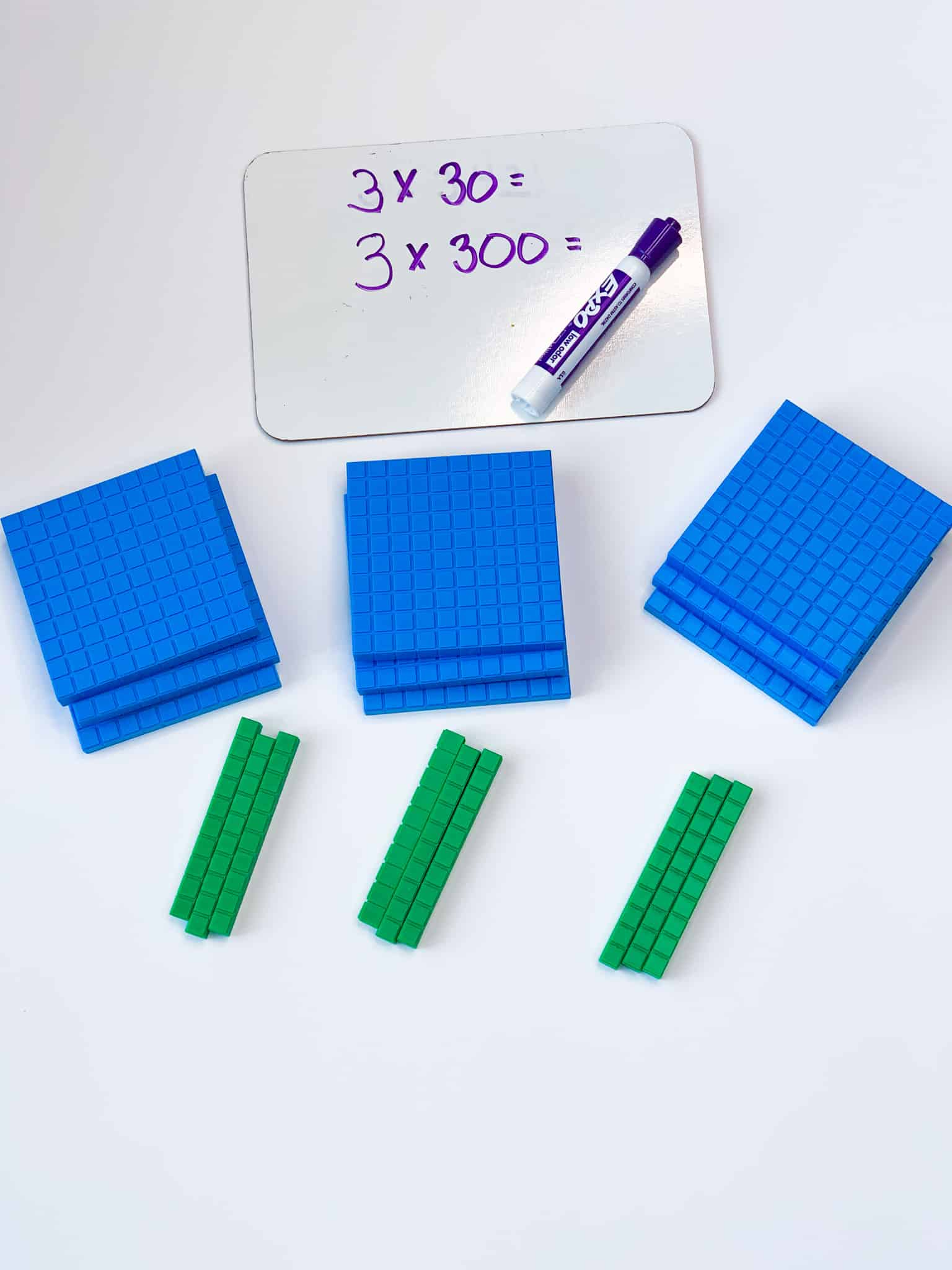 Small whiteboard with a math problem next to several sets of base-ten blocks for teaching the value of digits in math