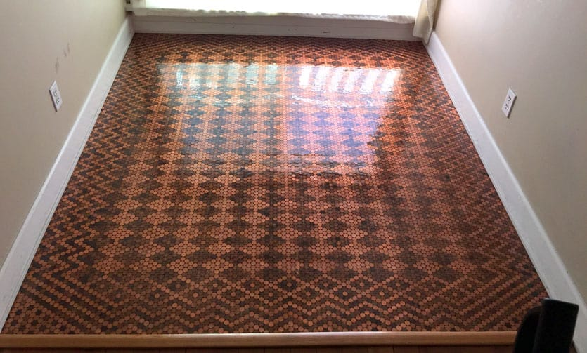 Floor covered in pennies in a design imitating an ornate rug