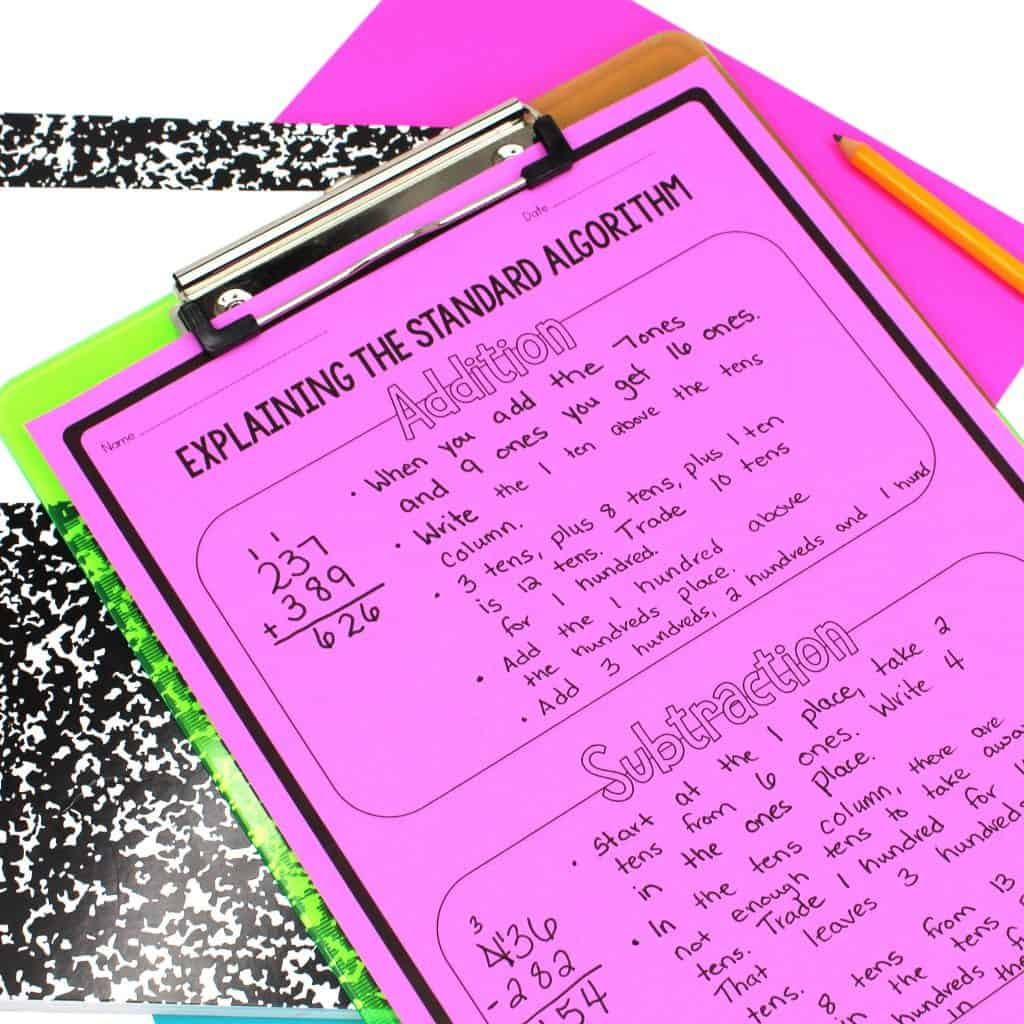 Addition and subtraction standard algorithm worksheet on neon pink paper on clipboard